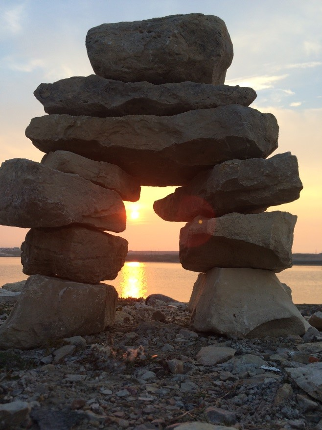 An Inukshuk at sunset stands on the shore between the Church and the ocean bay.